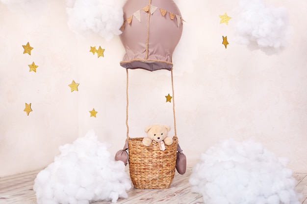 Teddy bear traveler and pilot. childhood dreams. stylish vintage children's room with aerostat, balloons and textile clouds