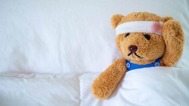 Плюшевый мишка был болен в постели после ранения в результате несчастного случая
