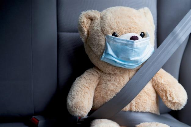 Teddy bear wearing a mask wearing a seatbelt in the car