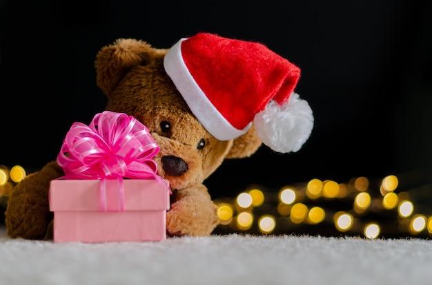 Плюшевый мишка в шляпе санта-клауса, держащей размытый фокус рождественской подарочной коробки.