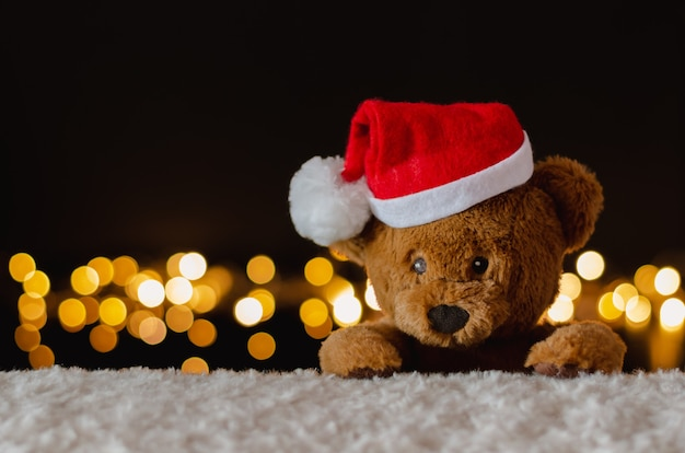 Плюшевый мишка в шапке санта-клауса с рождественскими огнями.