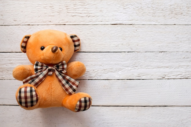 Teddy bear on white wooden background, copy space.