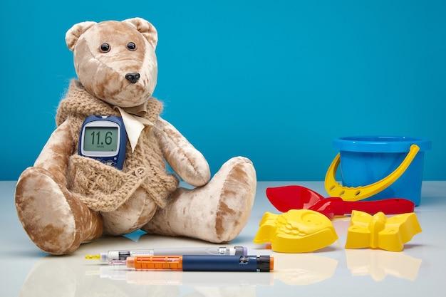 血糖値計とインスリン注射器のペンと青い壁に散らばった子供のおもちゃを持ったテディベア。小児、高血糖、小児科医における糖尿病治療の概念