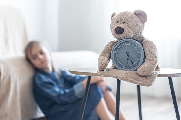 小さな女の子の部屋のぼやけた背景に目覚まし時計とテディベア。