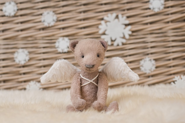 A teddy bear with angel wings sits on the background of a wicker basket.