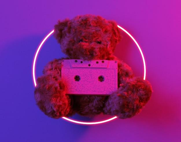 オーディオカセット付きのテディベア。 80年代のシンセウェーブとレトロウェーブの輝くサークルの未来的な美学