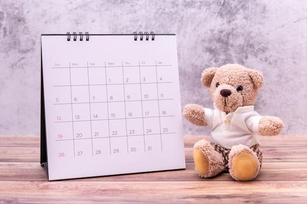 Teddy bear with calendar on wood table.