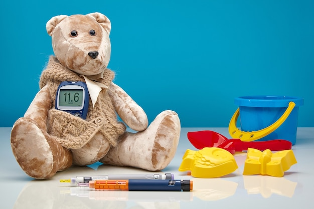 Teddy bear with a glucometer and insulin syringe pens and scattered children's toys on a blue wall. diabetes mellitus treatment concept in children, hyperglycemia, pediatrician