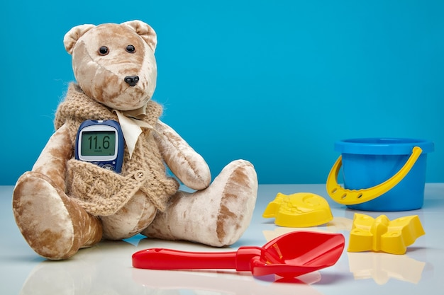 Teddy bear with a glucometer and scattered children's toys on a blue wall. the concept of treatment of diabetes in children, hyperglycemia, pediatric doctor