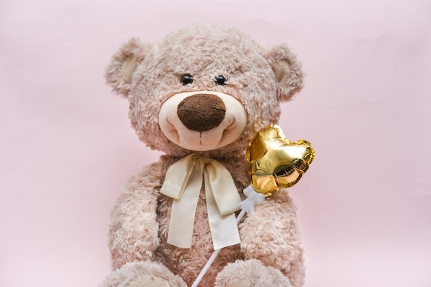 Teddy bear with a golden heart in a hug on a pink background.