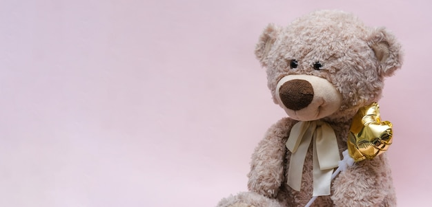 Teddy bear with a golden heart in a hug on a pink backgroundñŽ