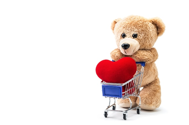 Teddy bear with heart shaped pillow in a cart