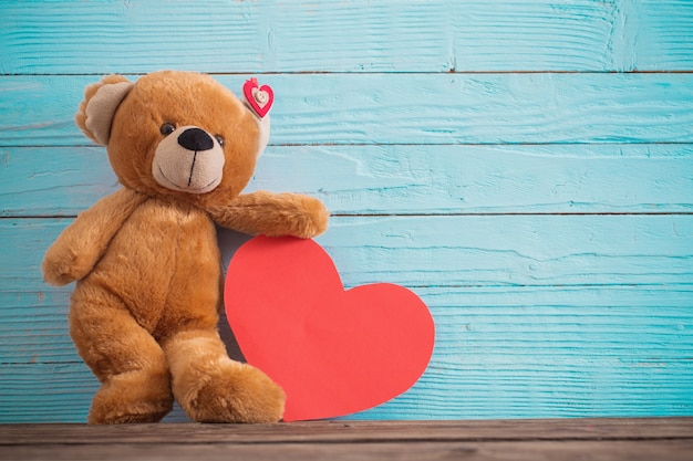 Teddy bear with red heart on old wooden background. valentine's day concept