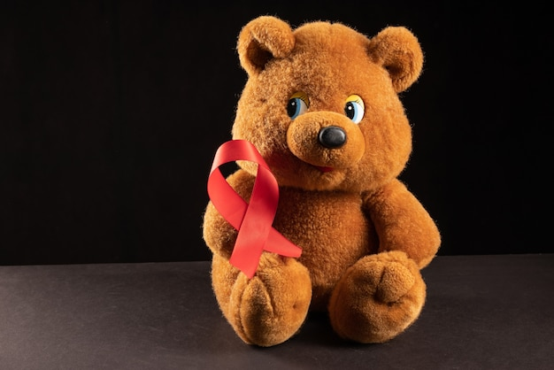 赤いリボンのhiv、暗い背景のエイズ、意識、医療サインとテディベア。コピースペース。