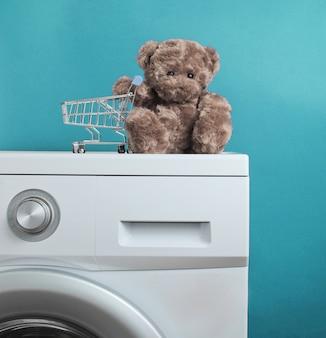 青い背景の洗濯機でショッピングカートとテディベア