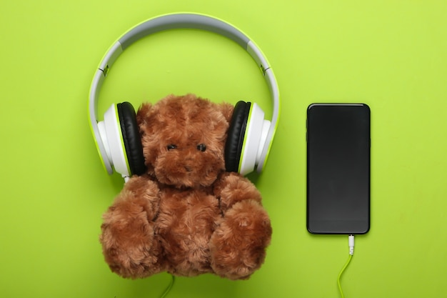 Teddy bear with stereo headphones and smartphone on a green surface