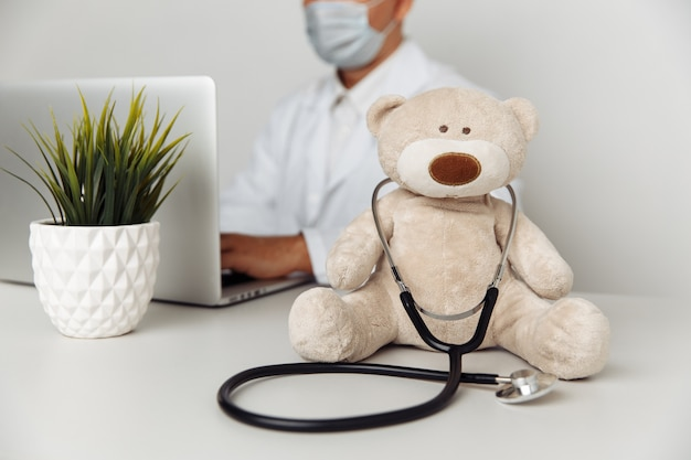 Teddy bear with stethoscope in pediatrician office child healtcare concept