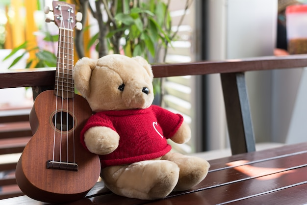 Teddy bear with ukulele on the balcony in the summer time.