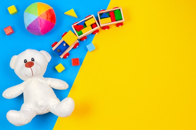 Teddy bear, wooden train, car, colorful blocks on blue and yellow background. top view