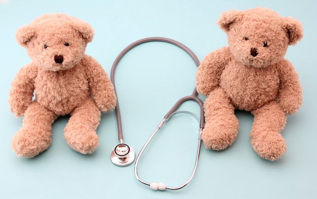 Teddy bears and medical equipment on blue