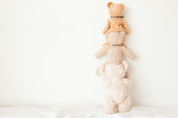 Teddy bears do a pyramid of acrobats, they are playful with a happy feel