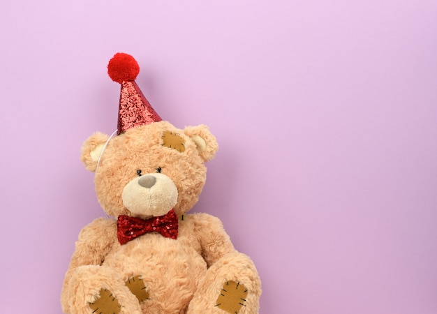 Teddy beige bear in a red cap sits, a place for an inscription
