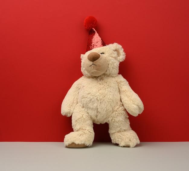 Teddy beige bear in a red cap