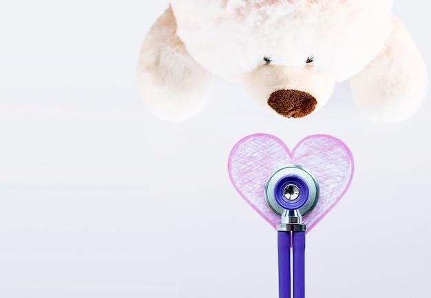 Teddy polar bear and phonendoscope on a light background