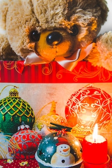 Teddybear in shopping bag with decorative christmas ornaments and lit candle