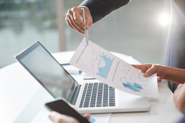 Современная компания teem коворкинг, используя графики и ноутбук в офисе