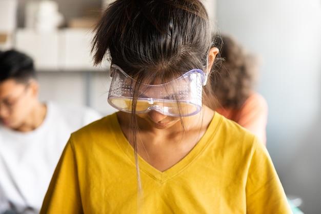 10代のアジアの女の子の高校生は、電子機器のクラス教育で目の保護ゴーグルを着用しています