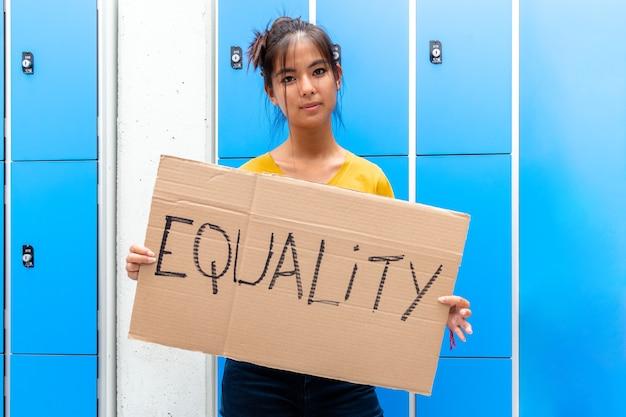 고등학교 평등에서 복수심에 불타는 평등 기호 배너를 들고 카메라를 보고 십 대 아시아 여자