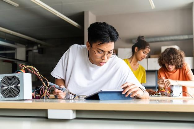 タブレットを使用して電子工学のクラス教育の指示を読む10代のアジアの高校生