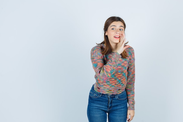 Teen beautiful girl with hand near mouth, looking away in sweater, jeans and looking curious , front view.