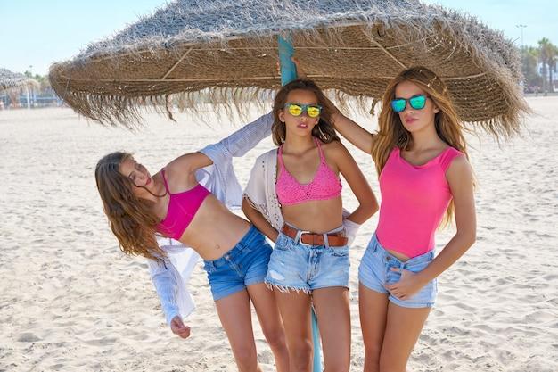 Teen best friends girls under thatch umbrella