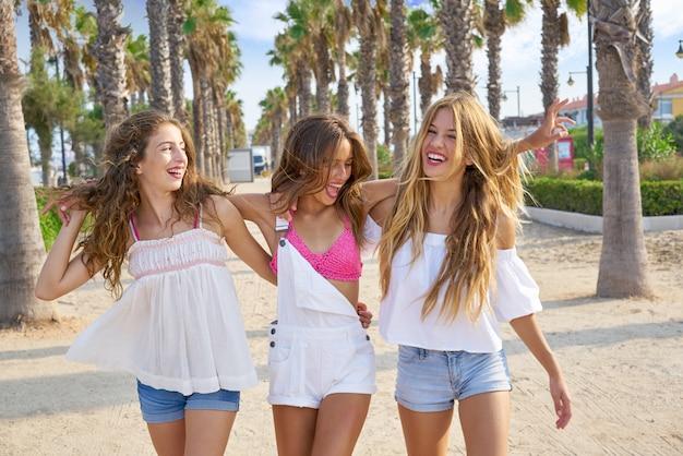 Teen best friends girls walking in palm trees