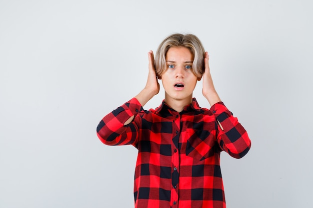 Maschio biondo teenager in camicia casual con le mani vicino alla testa e guardando spaventato, vista frontale.
