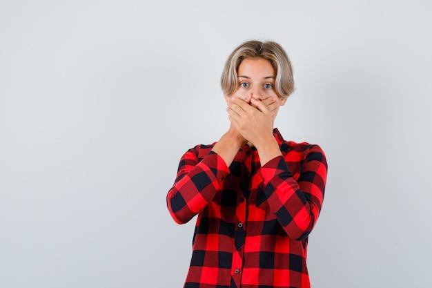 Подросток белокурый мужчина прикрывает рот руками в повседневной рубашке и выглядит потрясенным, вид спереди.