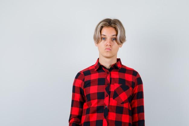 下唇を曲げて不機嫌そうに見える間、正面を見てカジュアルなシャツを着た10代の金髪の男性、正面図。