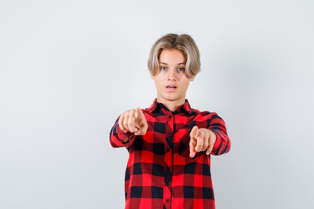 Подросток белокурый мужчина указывая на фронт в повседневной рубашке и выглядел уверенно. передний план.