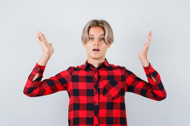 Подросток белокурый мужчина притворяется, что держит что-то в повседневной рубашке и выглядит озадаченным, вид спереди.
