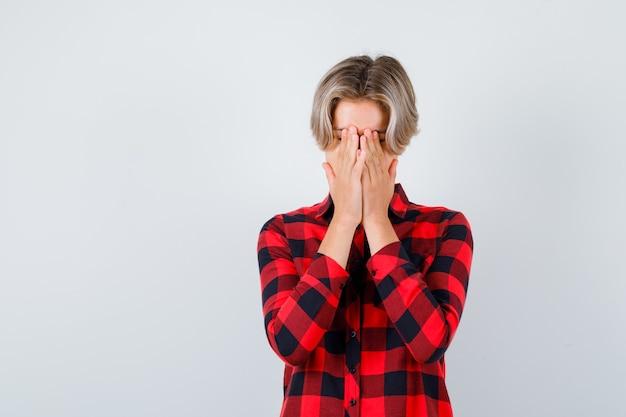 Подросток белокурый мужчина с руками на лице в повседневной рубашке и раздраженным взглядом, вид спереди.