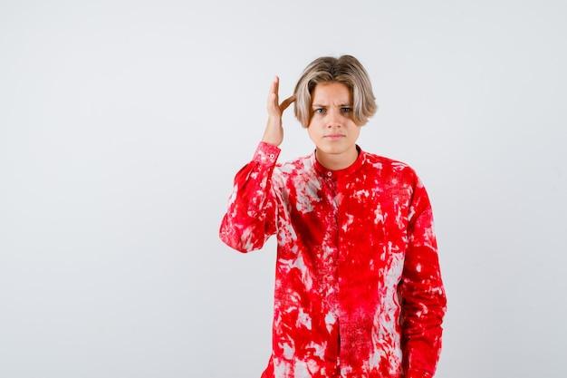 特大のシャツで頭に指を保ち、思慮深く、正面図を探している10代の金髪の男性。
