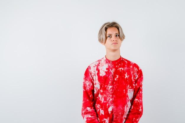 特大のシャツを着て目をそらし、思慮深く、正面図を探している10代の金髪の男性。