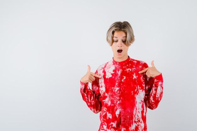 Maschio biondo teenager in camicia surdimensionata che indica se stesso e che sembra scioccato, vista frontale.
