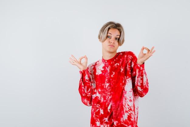 Maschio biondo teenager che mostra gesto giusto in camicia surdimensionata e sembra pensieroso. vista frontale.