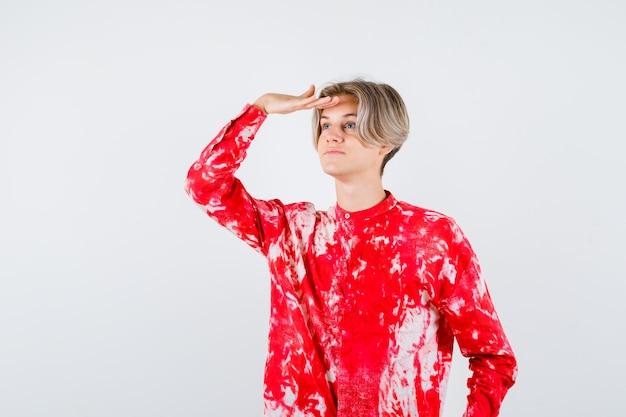 特大のシャツと物思いにふける、正面図ではっきりと見るために頭の上に手を持っている十代のブロンドの男性。