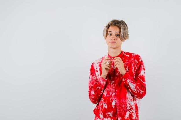 Maschio biondo teenager con le mani davanti a lui in camicia surdimensionata e sembra esitante. vista frontale.