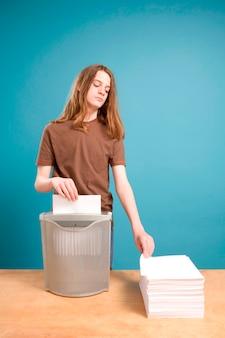 Teen boy in act of shredding blank paper