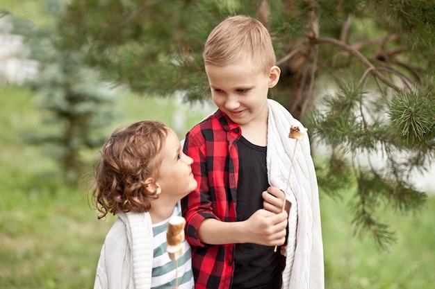 Подросток мальчик и девочка ребенок ест жареный зефир на открытом воздухе в лагере. путешествие, поход, отпуск, концепция кемпинга.